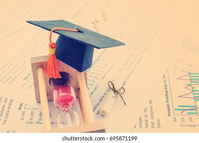 Graduate study abroad program concept : Graduation cap / hat on hour glass and a scroll of certificate nearby. Graduate study abroad program is a program that accept students from foreign countries.