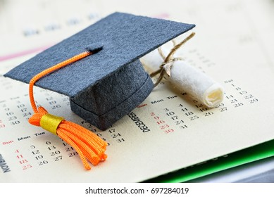 Graduate study abroad program concept : Graduation cap on a paper calendar and a scroll of certificate nearby. Graduate study abroad program is a program that accept students from foreign countries.