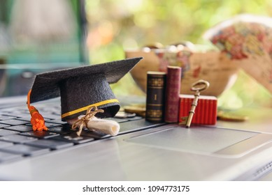 Graduate study abroad program for opening or expand world view concept : Graduation cap or hat, a key, world globe map, foreign text book on laptop, depicts achievement or success in online education