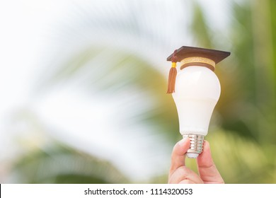 Graduate study, Education knowledge innovation and creativity concept: Hands holding light bulb with Graduated cap. Conceptual ideas Educational for successs study or business world. Back to School