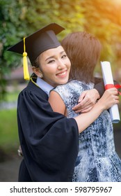 Graduate woman students wearing graduation hat and gown, hugging her mother