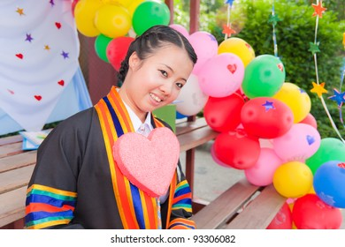 Graduated Asian girl with Pink heart and colorful balloons in background