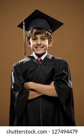 Graduated boy with mortarboard smiling with arms crossed