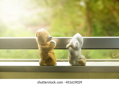 Graduated light, selective focus on bear and sheep doll kneeling praying each other on the train journey. Will you marry me?