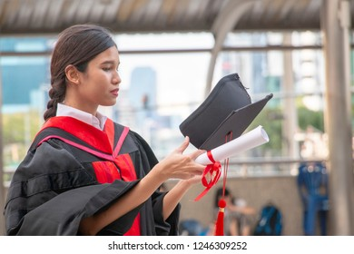 Graduated woman is holding hat and black gown