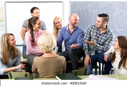 Graduates at extension courses are having a conversation with each other and their professor during a break in a classroom