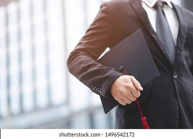 Graduates of the University, businessman holding hats along with success,  filter tone outdoor sunny in the morning. office background. New graduate start working on the first day. Education concept.