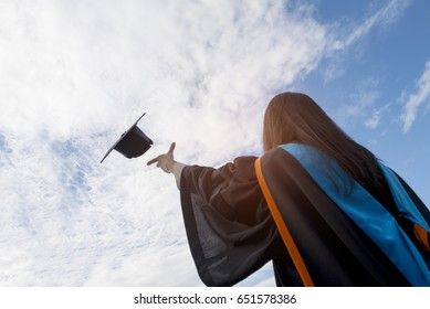 Graduates of the University,Of graduates holding hats handed to the sky.