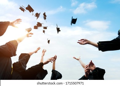Graduating students hands throwing graduation caps in the air.