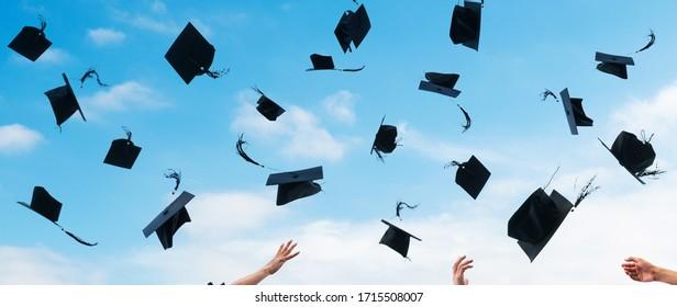 Studierende, die ihre Schulabschlüsse in die Luft werfen.