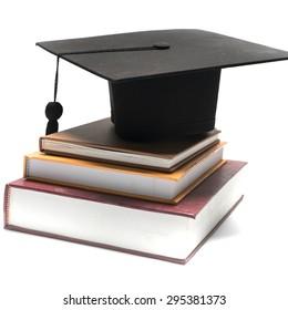 Graduierungskappe und Buch einzeln auf weißem Hintergrund