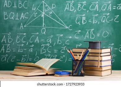 Graduierungsmütze mit Büchern auf dem Hintergrund der Tafel im Auditorium