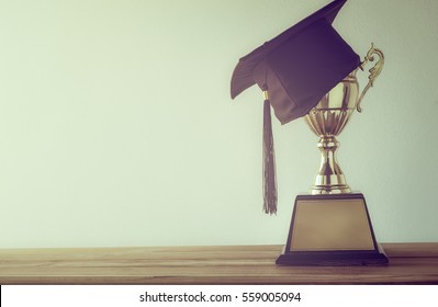 graduation cap with champion golden trophy on wood table with copy space ready for your design.graduation, success, education, concept