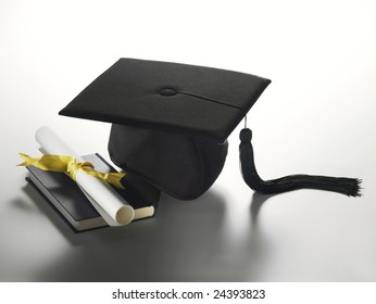 A graduation cap with a diploma and book