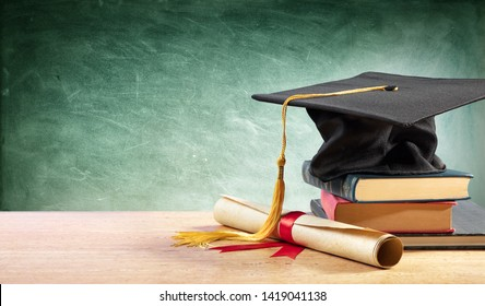 Graduation Cap And Diploma On Table With Books