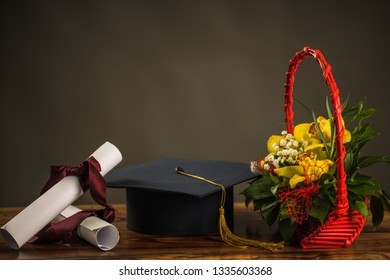 Graduation cap, hat with degree paper and flower bouquet on retro wood table.