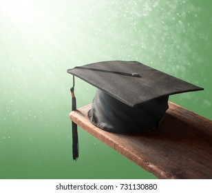 graduation cap, hat on wood with abstract green background graduation concept.