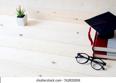 Graduation cap, hat on wood table graduation concept.