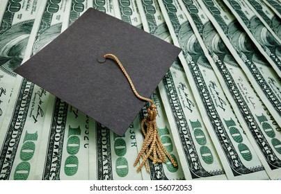 graduation cap on assorted hundred dollar bills - education concept