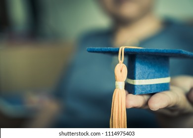 Graduation cap on hands show success in education learning study international abroad in university with blur students, copy space for design. Back to School