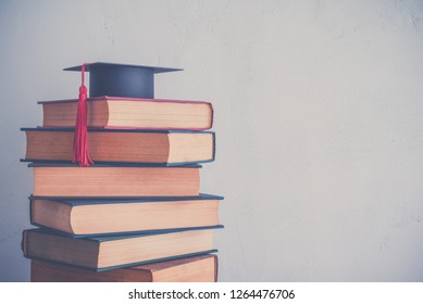 Graduation cap on stack of many antique books on shelf in book store or library room with white wall background. Knowledge learning, education, bachelor degree in university or back to school concept.