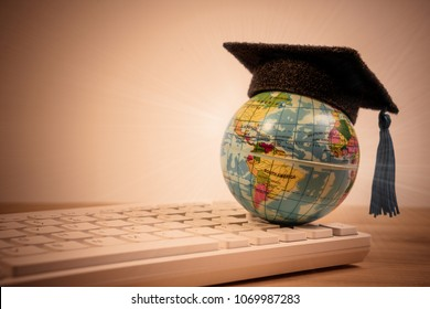Graduation cap on top earth globe model map on computer keyboard background. Graduate study abroad program or graduate study abroad concept.