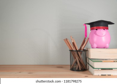 Graduation cap with piggy bank on books.