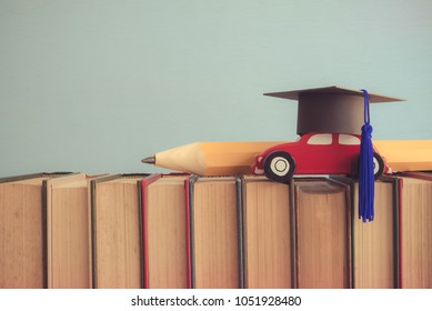 Graduation cap, wooden car and big pencil over the books on blue wall background - Education concept