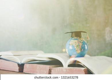 Graduation cap with World globe on text book. Graduate study abroad programs. International education school Concept.