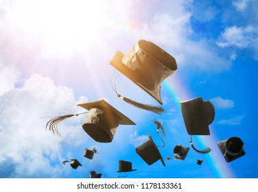 Graduation caps, hat thrown in the air with sun ray blue sky abstract background.