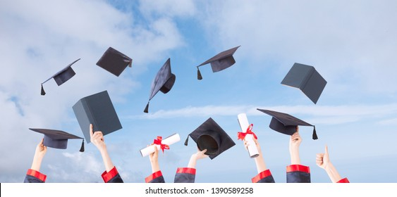 graduation ceremony hats and hands up in sunny sky