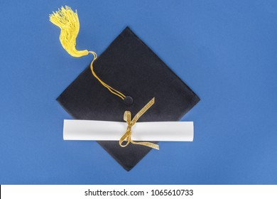 Graduation concept with diploma and graduation cap isolated on blue