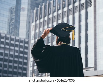 Graduation day, Back view of Asian woman with graduation cap and gown holding diploma, Successful concept
