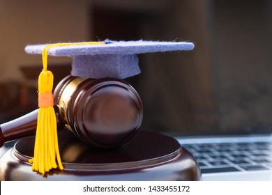 Graduation diploma hat / Judge gavel on computer notebook. Concept of graduate online study international abroad about jurisprudence laws certificate in university distance education for learning.