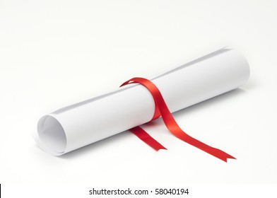 Graduation diploma scroll tied with red ribbon on white background