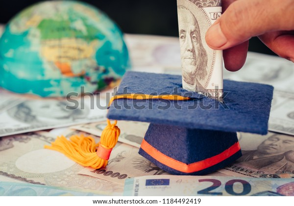 Graduation fund for save moneys graduate study higher degree education in future. Business or Student hand dropping investing US Dollar bill money to Education savings and investment ideas