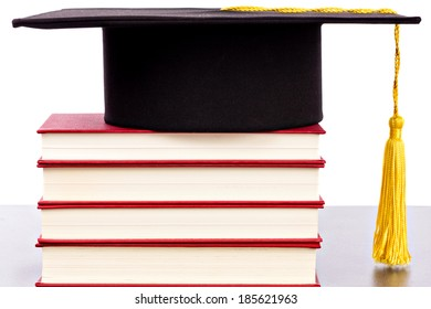 Graduation hat and books against white background
