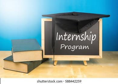 Graduation hat, books, blackboard with text internship program on a wooden background.