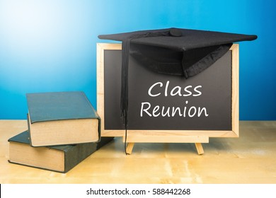 Graduation hat, books, blackboard with text class reunion on a wooden background.