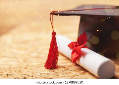 Graduation hat and diploma on wooden background
