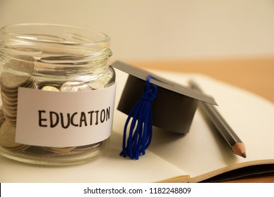 Graduation hat with glass jar saving money scholarship for education in future on wood table,vintage.