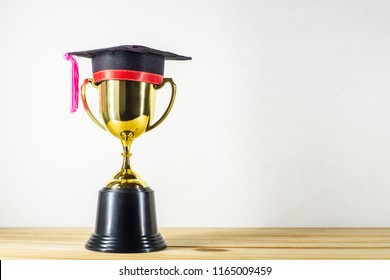 graduation hat with golden trophy on wood table
