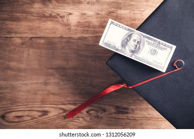 Graduation hat and money on wooden table.