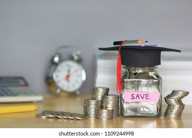 Graduation hat on coins money in the glass bottle on white background, Saving money for education concept