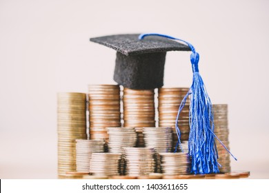 Graduation hat on coins money on white background. Saving money for education or scholarship concepts. Conception of education fee, education expenses, school tuition cost, graduation cap with coin.