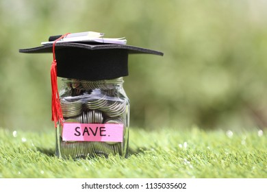 Graduation hat on the glass bottle on natural green background, Saving money for education concept