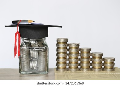 Graduation hat on the glass bottle with Stack of coins money on wtite background, Saving money for education concept