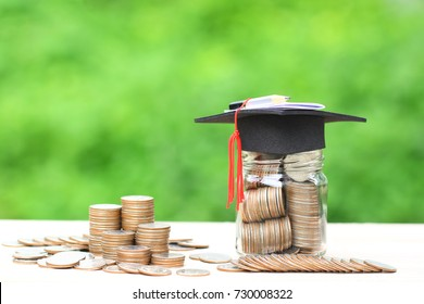 Graduation hat on the glass bottle with Stack of coins money on natural green background, Saving money for education concept