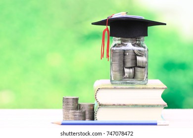 Graduation hat on the glass bottle and books on natural green background, Saving money for education concept
