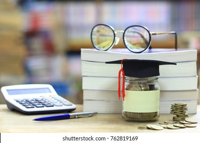 Graduation hat on the glass bottle on bookshelf in the library room background, Saving money for education concept